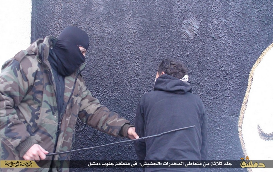 A masked IS fighter is seen whipping one of the drug addicts