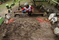 Tomb digger cleans up Hayati Lutfiah Hamid\'s grave, the first identified victim of the AirAsia flight QZ8501 crash at Sawo Tratap Islamic cemetery on January 2, 2015