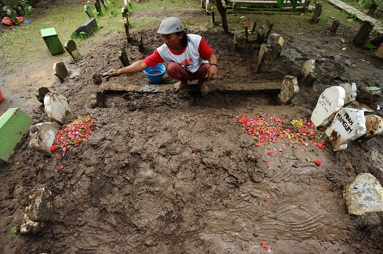 Tomb digger cleans up Hayati Lutfiah Hamid's grave, the first identified victim of the AirAsia flight QZ8501 crash at Sawo Tratap Islamic cemetery on January 2, 2015