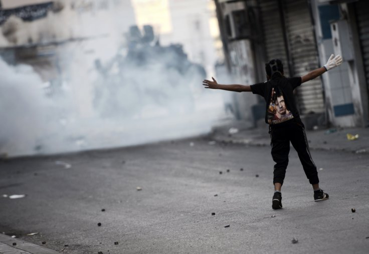 A Bahraini protestor gestures towards riot police during clashes following a protest against the arrest of the head of the banned Shiite opposition movement Al-Wefaq, Sheikh Ali Salman