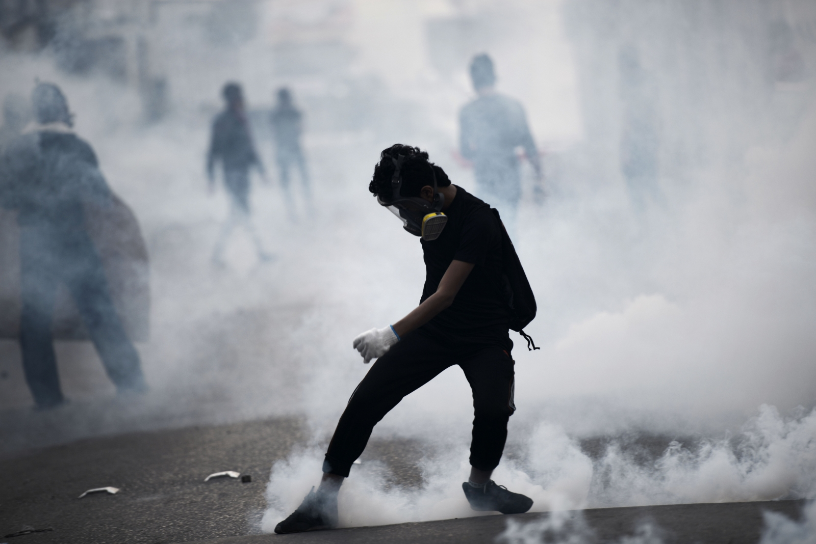 A Bahraini protester kicks back a tear gas canister during clashes with riot police following a protest against the arrest of the head of the banned Shiite opposition movement