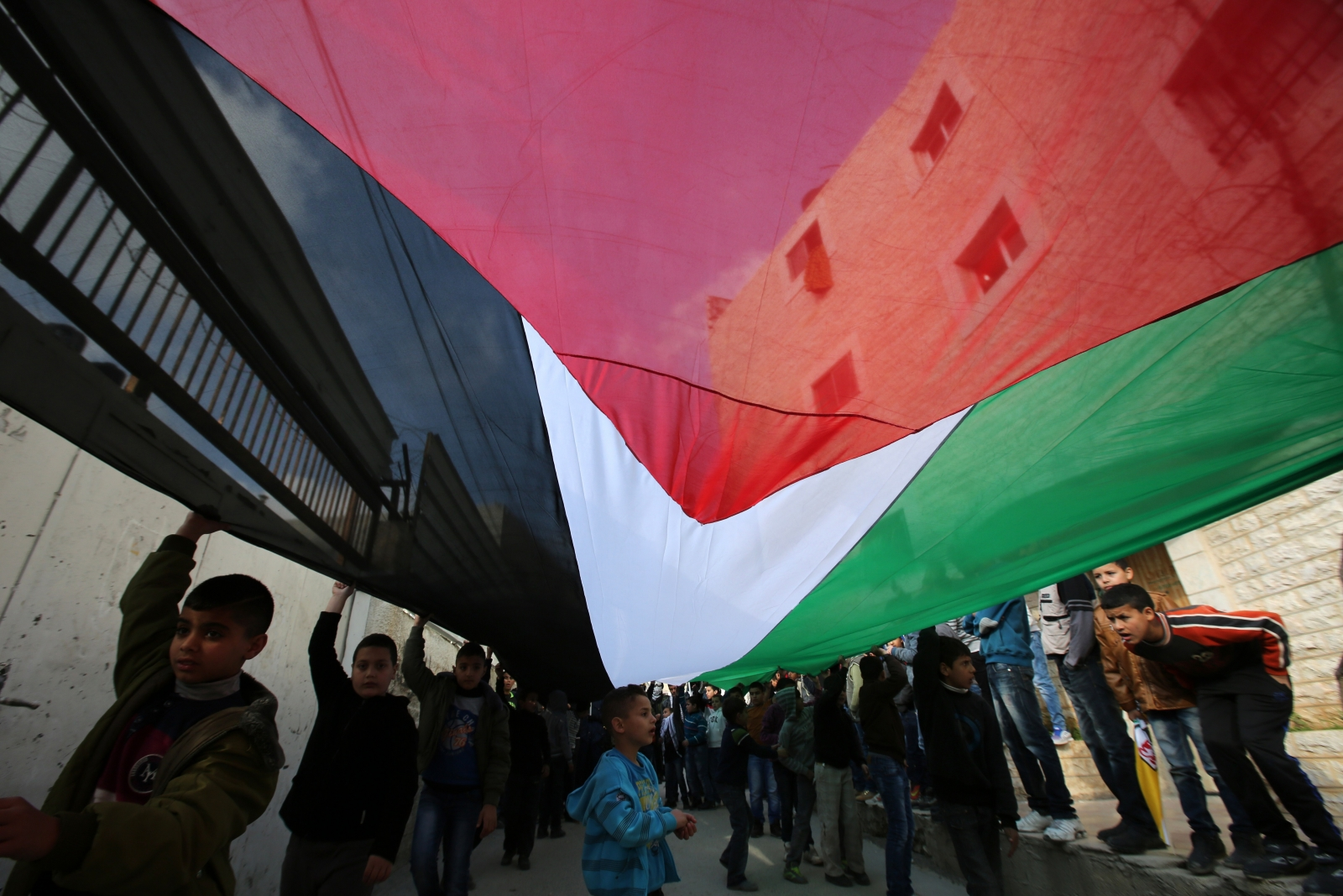 Palestinian children deploy a giant national flag during a march of members of the al-Aqsa Martyrs Brigades, the Palestinian Fatah movement's armed wing, to mark the 50th anniversary of the launching of Fatah's armed struggle against Israel