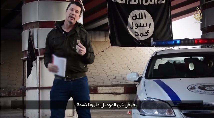 John Cantlie poses next to an Islamic State police car