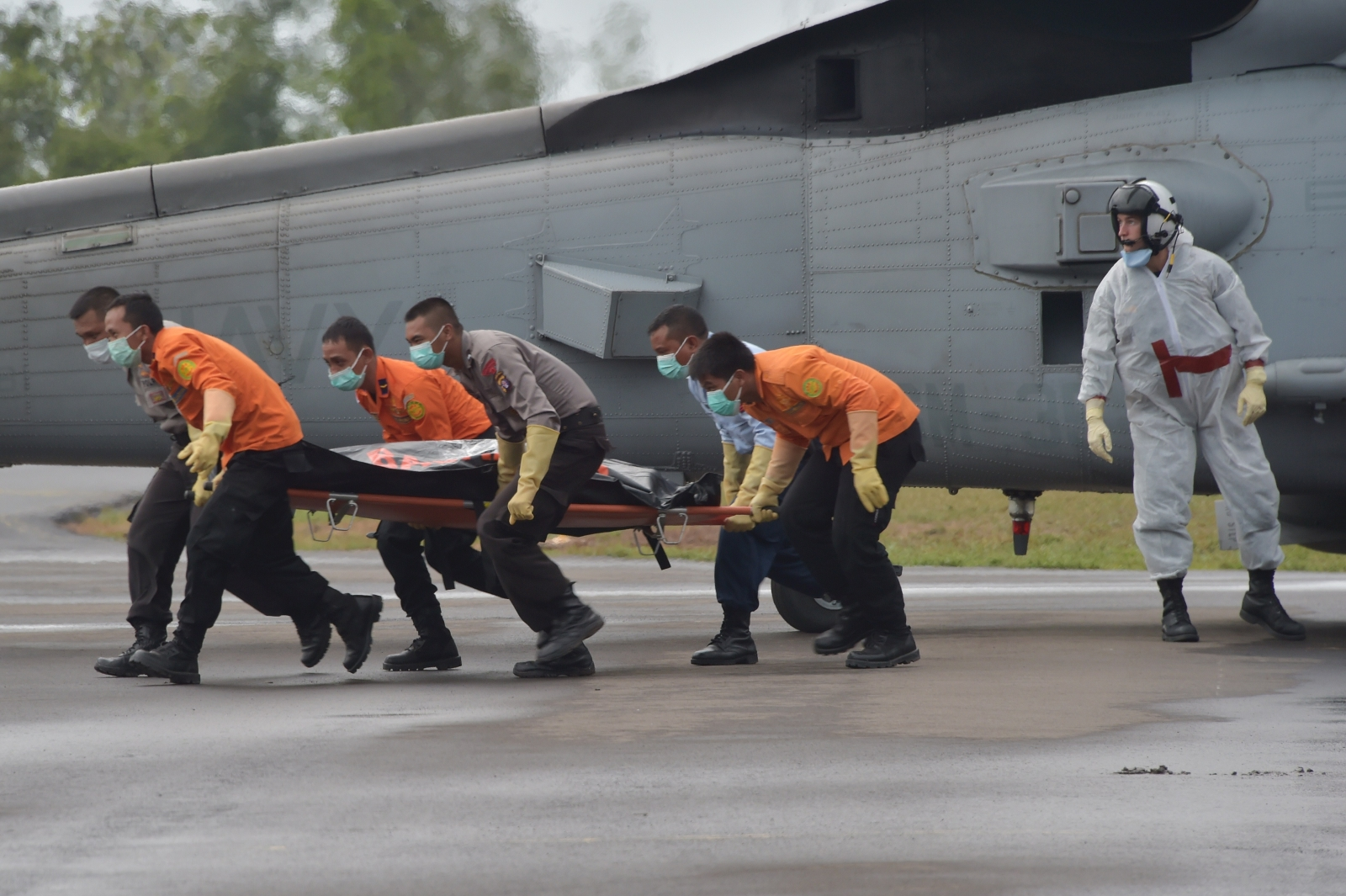 Members of an Indonesian search and rescue team collect a bag containing a victims body of AirAsia flight 8501, from a US navy helicopter Seahawk. (ADEK BERRY/AFP/Getty Images)