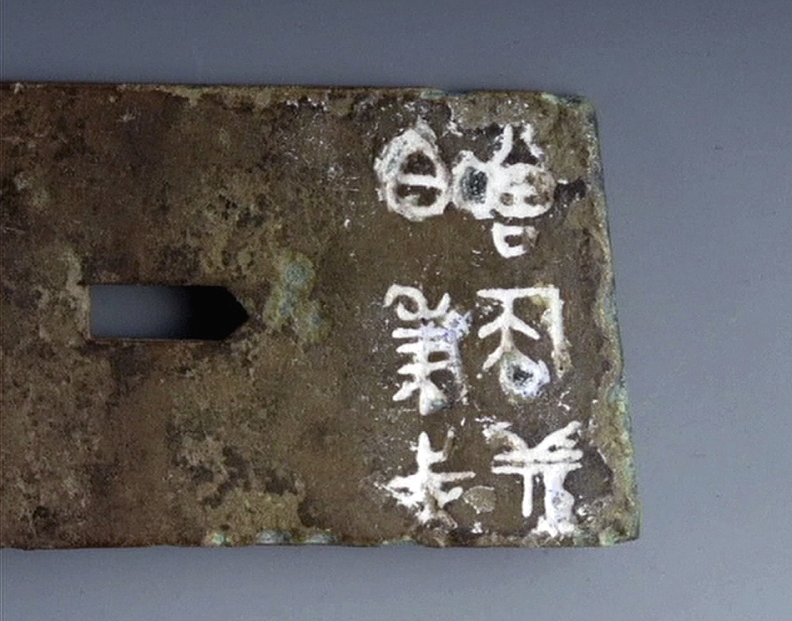 Close-up of the Old Chinese characters inscribed on the metal item