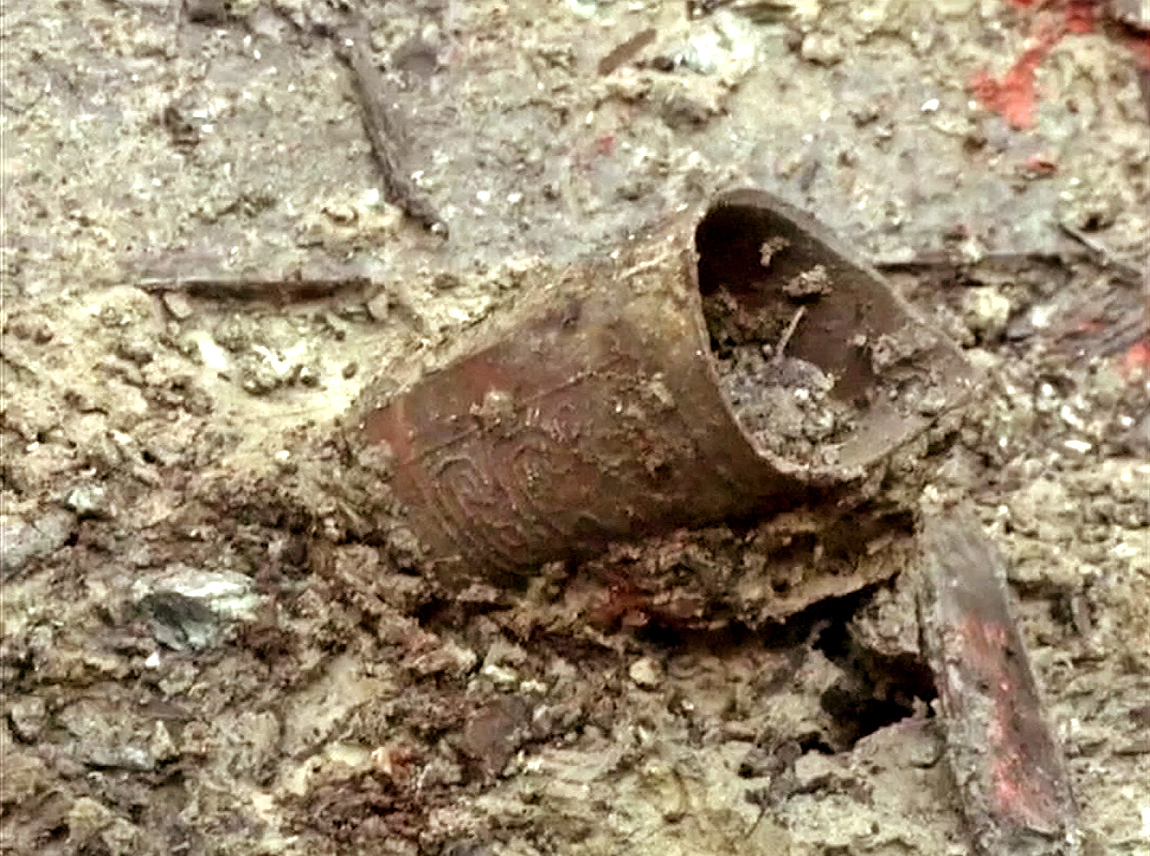 A beautifully inscribed metal object being unearthed from the tomb