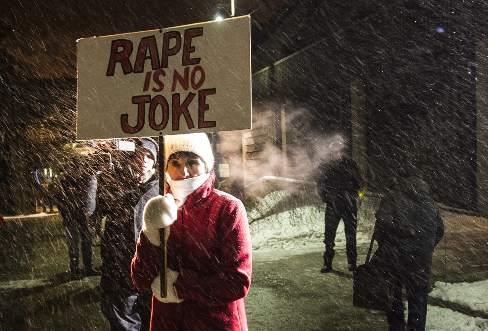 "A woman holding a sign that reads ""Rape is No Joke"" protests as people walk into the Centre In The Square venue where Bill Cosby is performing in Canada"