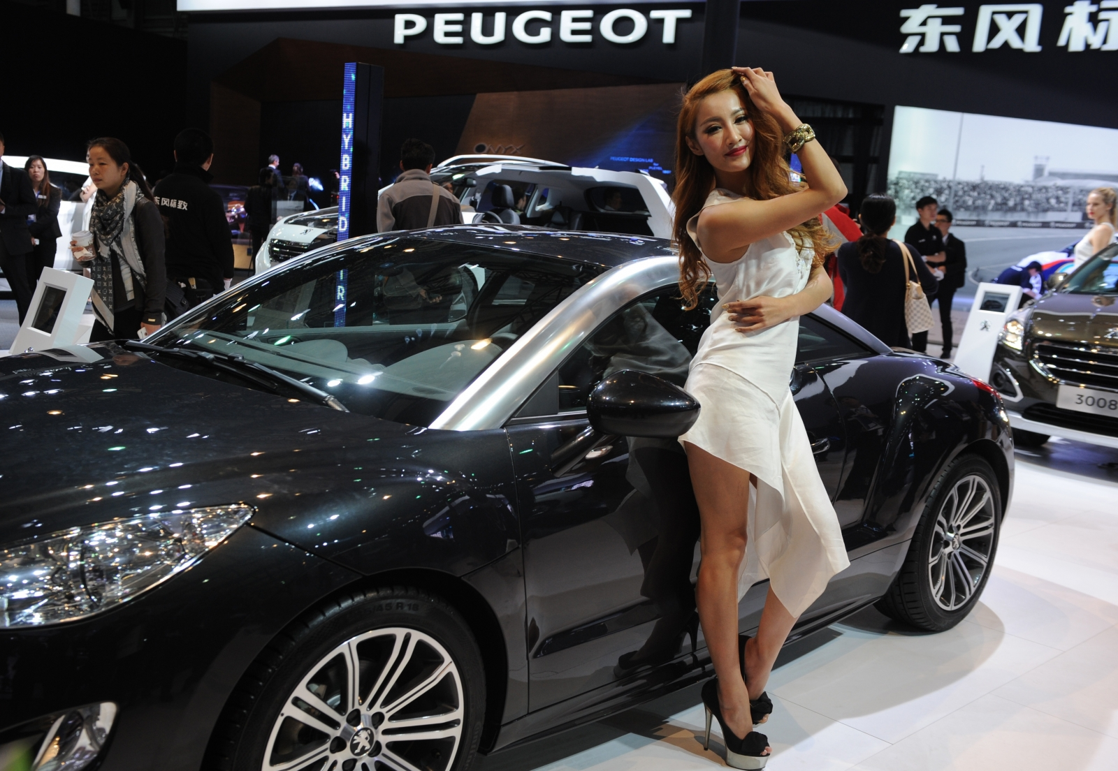 A model poses beside a vehile at the 2013 Shanghai car show (Getty)