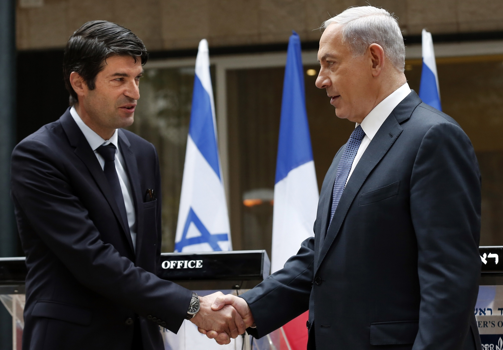 Israeli Prime minister Benjamin Netanyahu (R) shakes hands with French Ambassador to Israel Patrick Maisonnave after presenting his condolences following the deadly attack on French satirical newspaper Charlie Hebdo on January 9, 2015 at the Prime Ministe