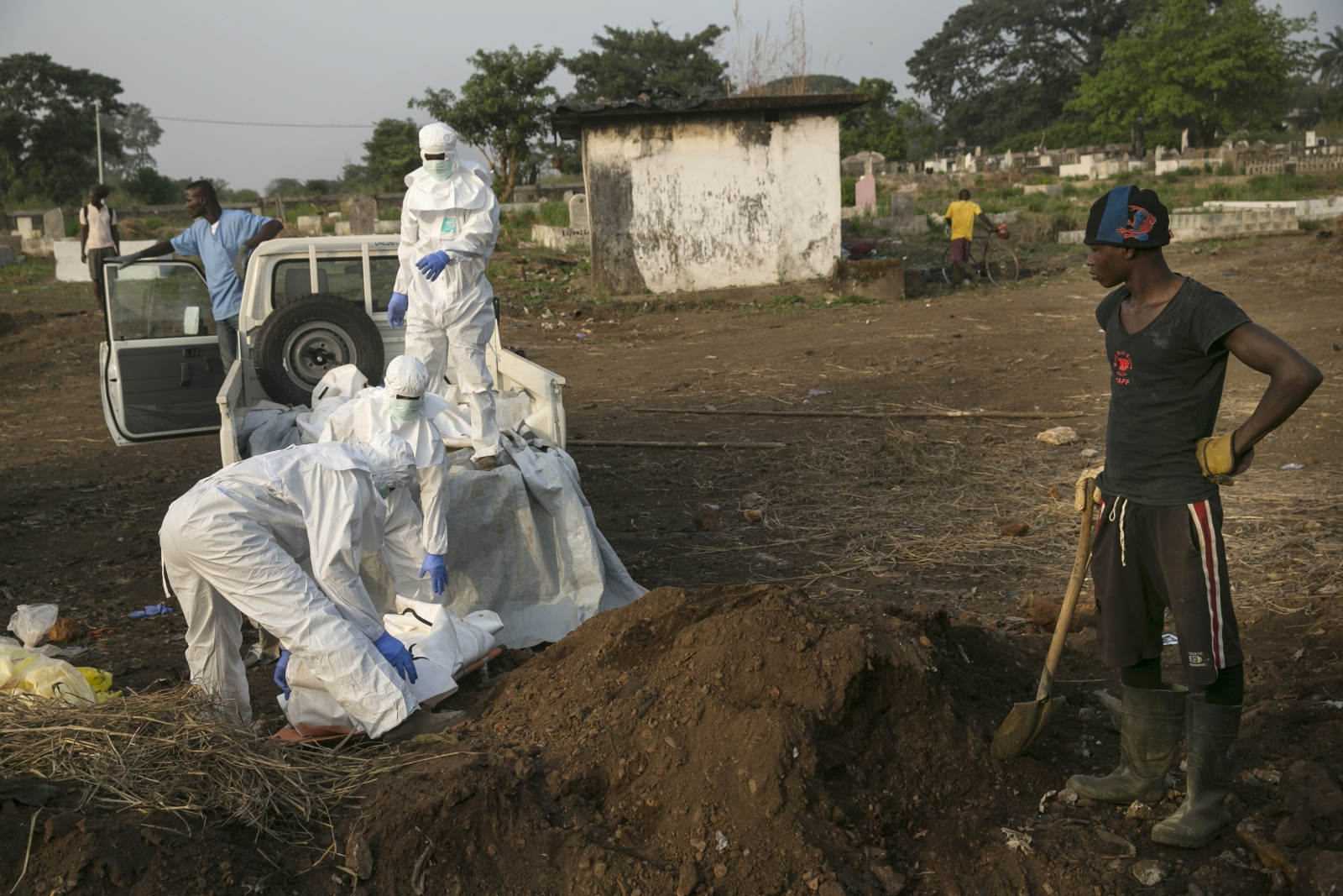A grave digger waits as health workers unload the bodies of Ebola victims for burial at a cemetery