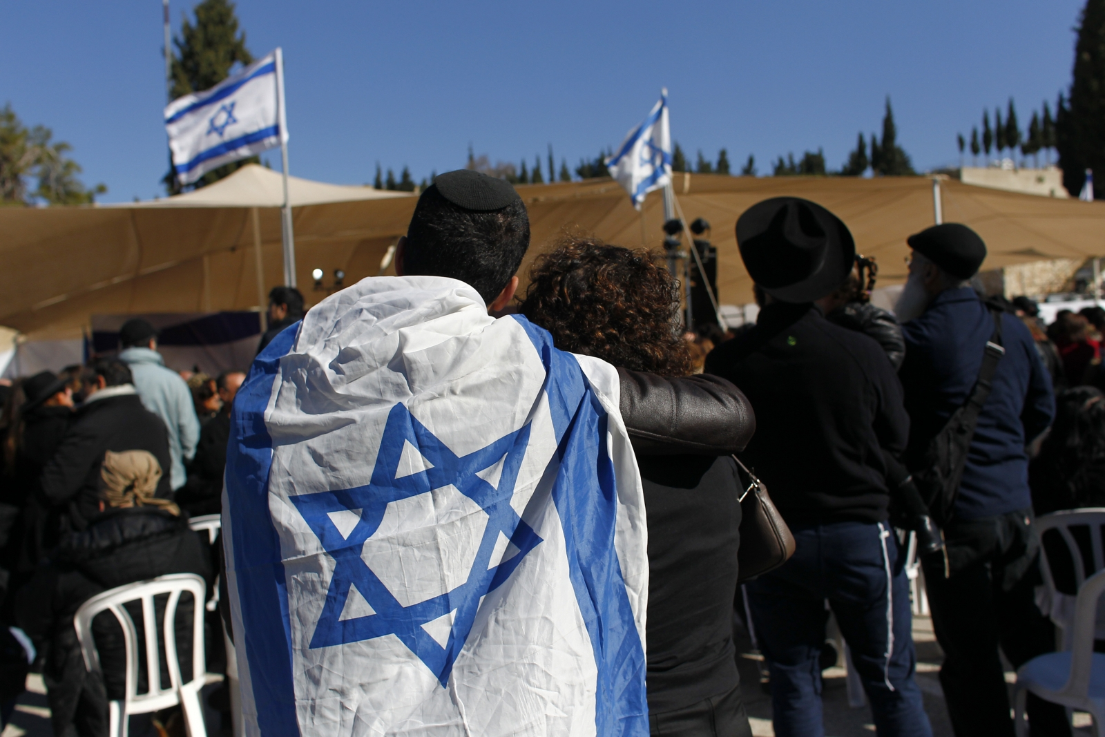 A mourner with an Israeli flag draped over his shoulder attends the joint funeral of the four French Jews killed in the attack on a Paris kosher supermarket