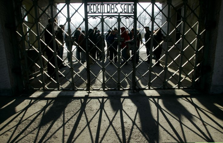 People at a gate in Buchenwald concentration camp, reading: 'To each his own'