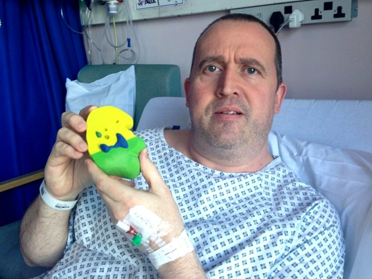 John Cousins holds up a 3D-printed model of his kidney from hospital