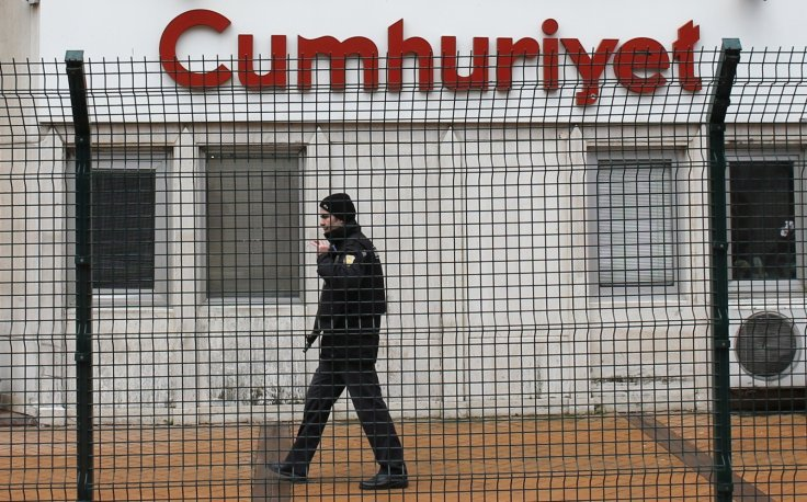 A private security employee stands guard at the entrance of daily newspaper Cumhuriyet's offices