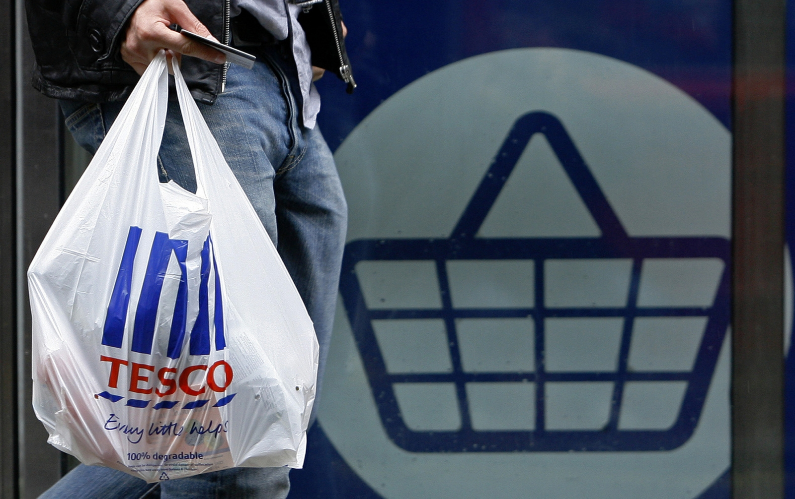 A man carries a carrier bag as he leaves a Tesco supermarket in London