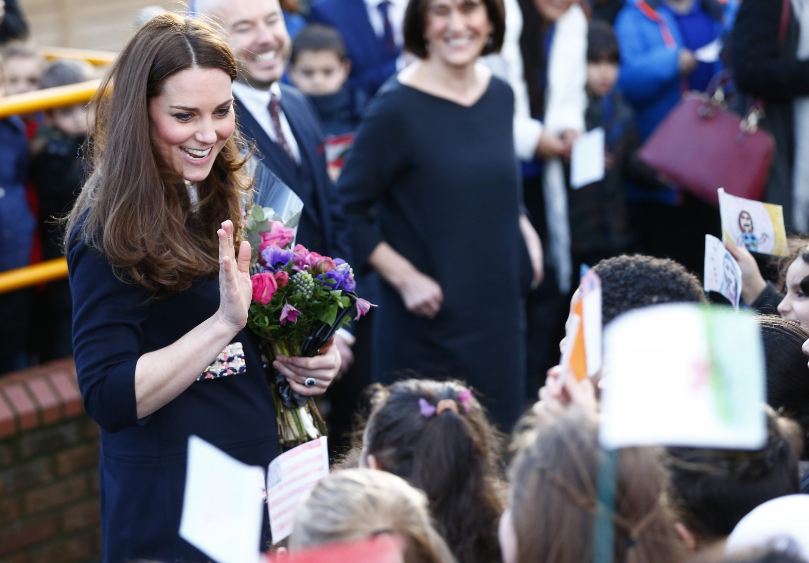 Duchess of Cambridge shows off beginnings of baby bump during school visit