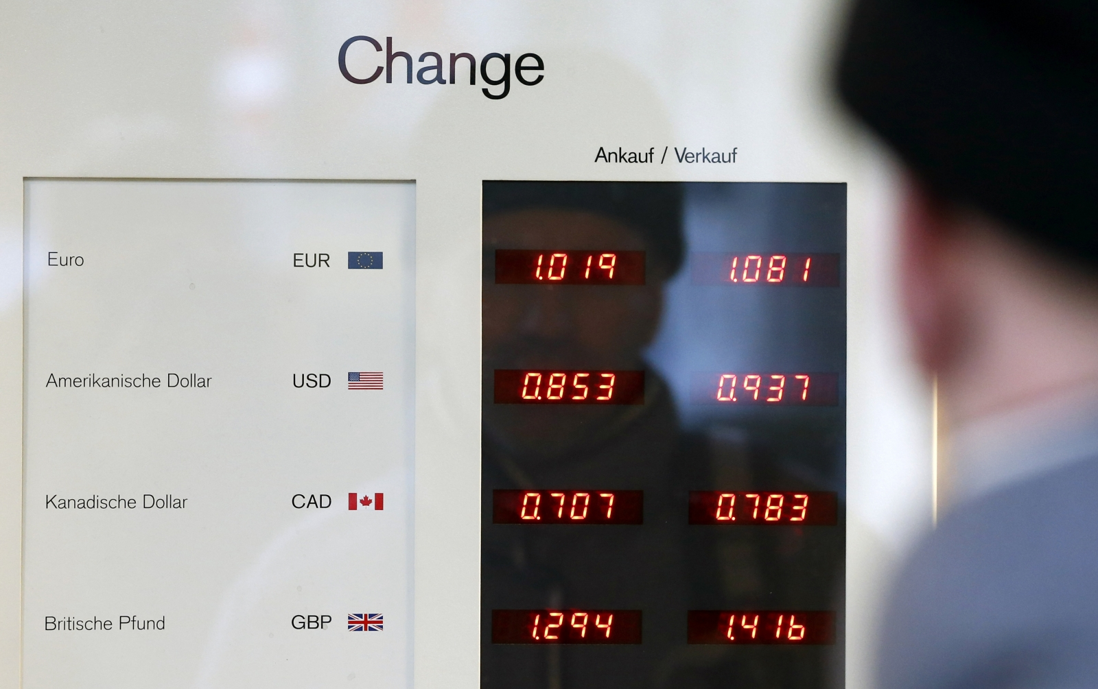 A man looks at a board showing currency exchange rates in Bern January 15, 2015. The Swiss National Bank shocked financial markets on Thursday by scrapping a three-year-old cap on the franc, sending the safe-haven currency soaring against the euro and sto