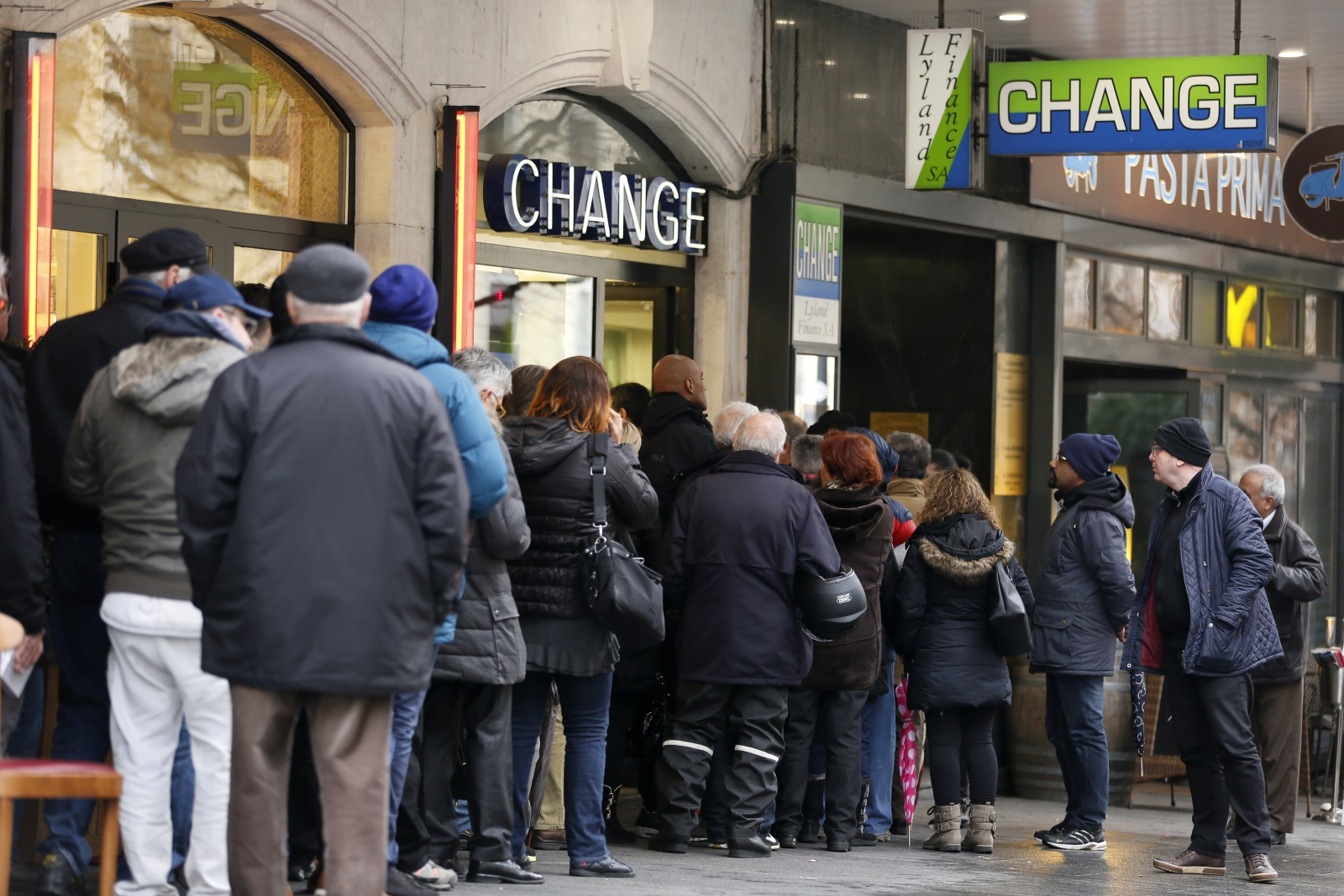 People queue outside a currency exchange office in Geneva, January 16, 2015. Swiss stocks sank on Friday, extending the sell-off sparked by the Swiss National Bank's surprise decision to remove a ceiling on the Swiss franc that sent the currency soaring.