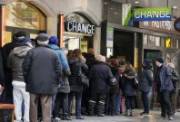 People queue outside a currency exchange office in Geneva, January 16, 2015. Swiss stocks sank on Friday, extending the sell-off sparked by the Swiss National Bank\'s surprise decision to remove a ceiling on the Swiss franc that sent the currency soaring.
