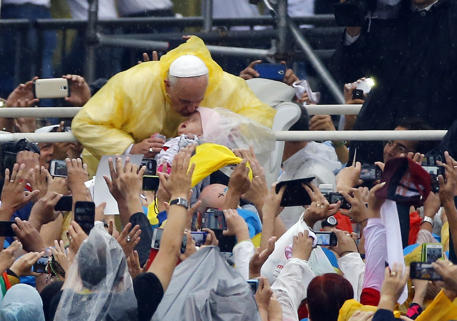 Pope Francis kisses a child as he arrives to lead an open-air Mass at Rizal Park in Manila