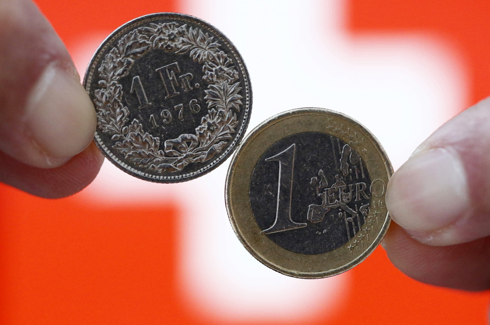 A one Swiss franc coin (L) and a one Euro coin are seen in front of a Swiss flag in this illustration picture in Bern January 18, 2015.