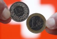 A one Swiss franc coin (L) and a one Euro coin