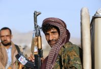 A Houthi fighter holds a rifle with a sticker portraying Ahmed Ali Abdulah Saleh, the eldest son of Yemen\'s former president Ali Abdullah Saleh