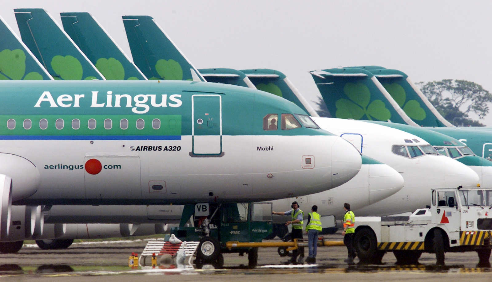 Ground crew are seen parking an Aer Lingus Airbus A320 away from the passenger terminals at Dublin Airport, in the Republic of Ireland in this June 2, 2002 file photograph