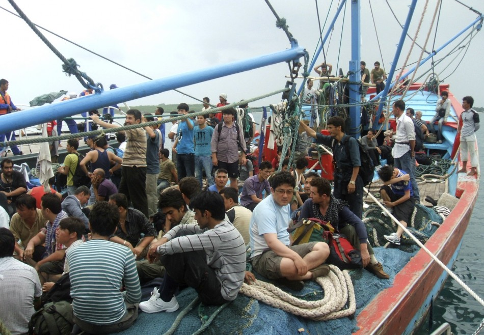 Asylum seekers sit on a fisherman's boat after they were rescued when their boat sunk off Sunda straits