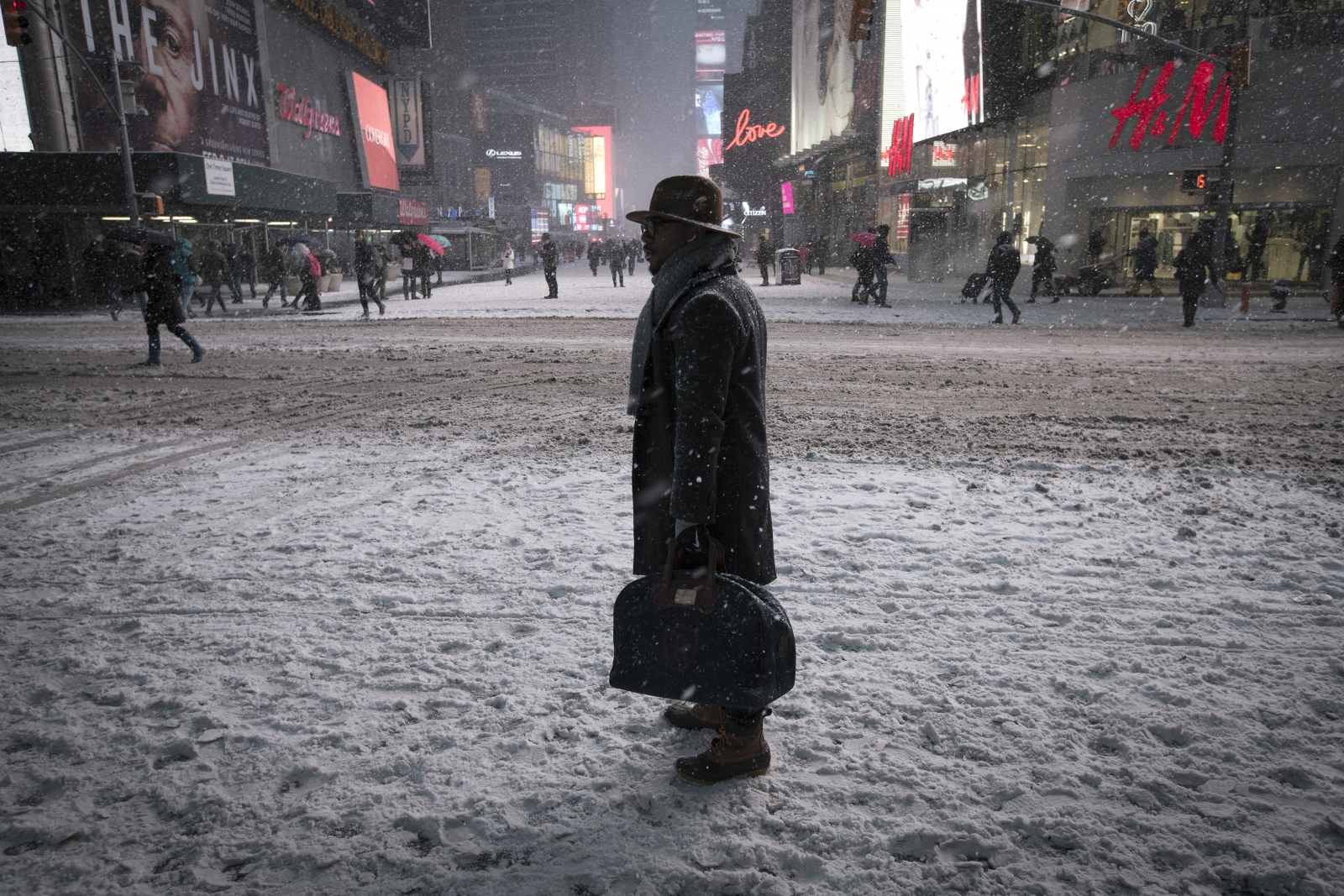 A man stands in falling snow on West 42nd street in Times Square in New York, January 26, 2015.