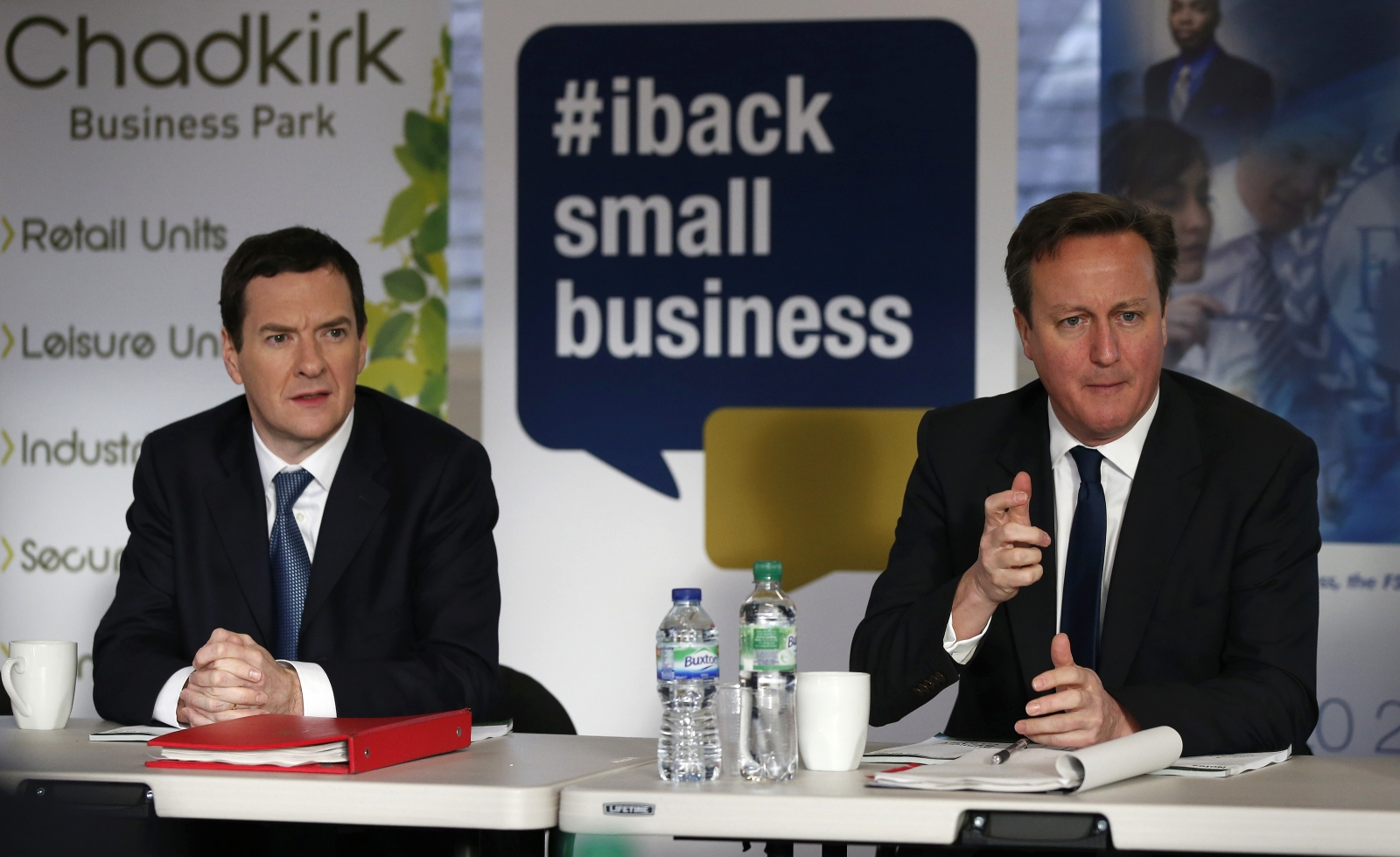 Britain's Prime Minister David Cameron (R) sits with Chancellor George Osborne during a meeting with local small business owners in Stockport, northern England January 9, 2015.
