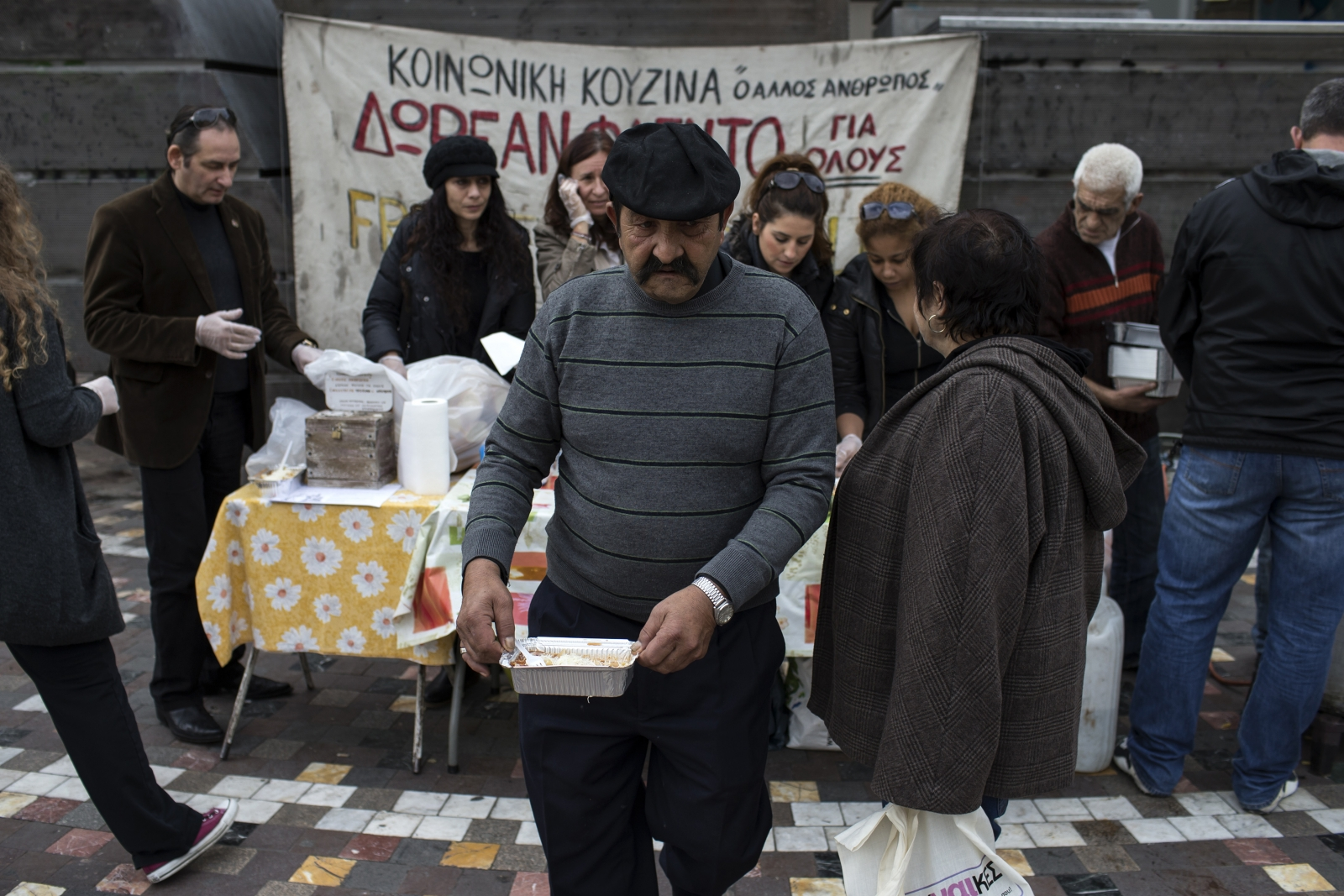 A man receives a portion of food at a soup kitchen, organized during the years of the Greek economic crisis by