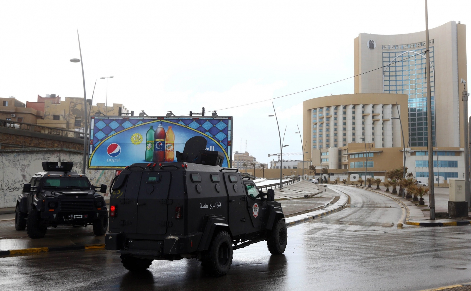 Libyan security forces and emergency services surround Tripoli's central Corinthia Hotel (R) on January 27, 2015 in the Libyan capital