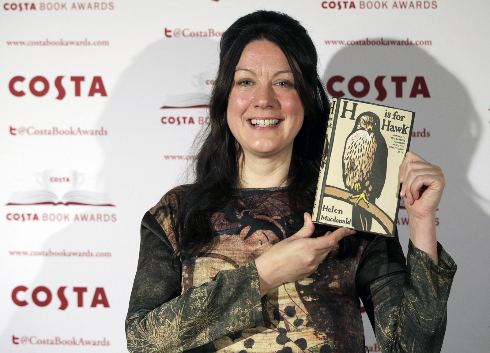 "Helen MacDonald, nominee in the 2014 Costa Book Awards and winner of the Costa Biography Award category, poses with her book ""H is for hawk"""