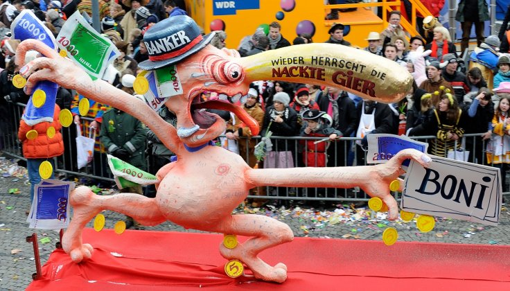 A Rosenmontag float depicts a grasping banker (Getty)