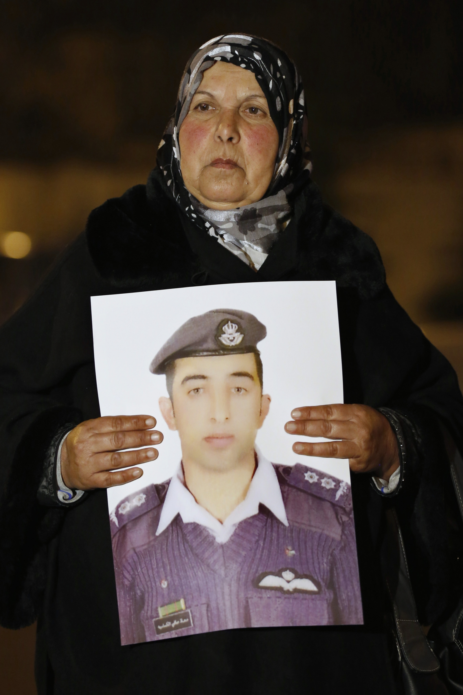 Mother of Islamic State captive Jordanian pilot Muath al-Kasaesbeh holds his picture as she takes part in a demonstration demanding that the Jordanian government negotiate with Islamic state