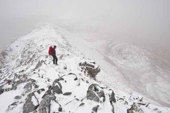 A hiker on the ridge of Beinn Damh in the Scottish Highlands