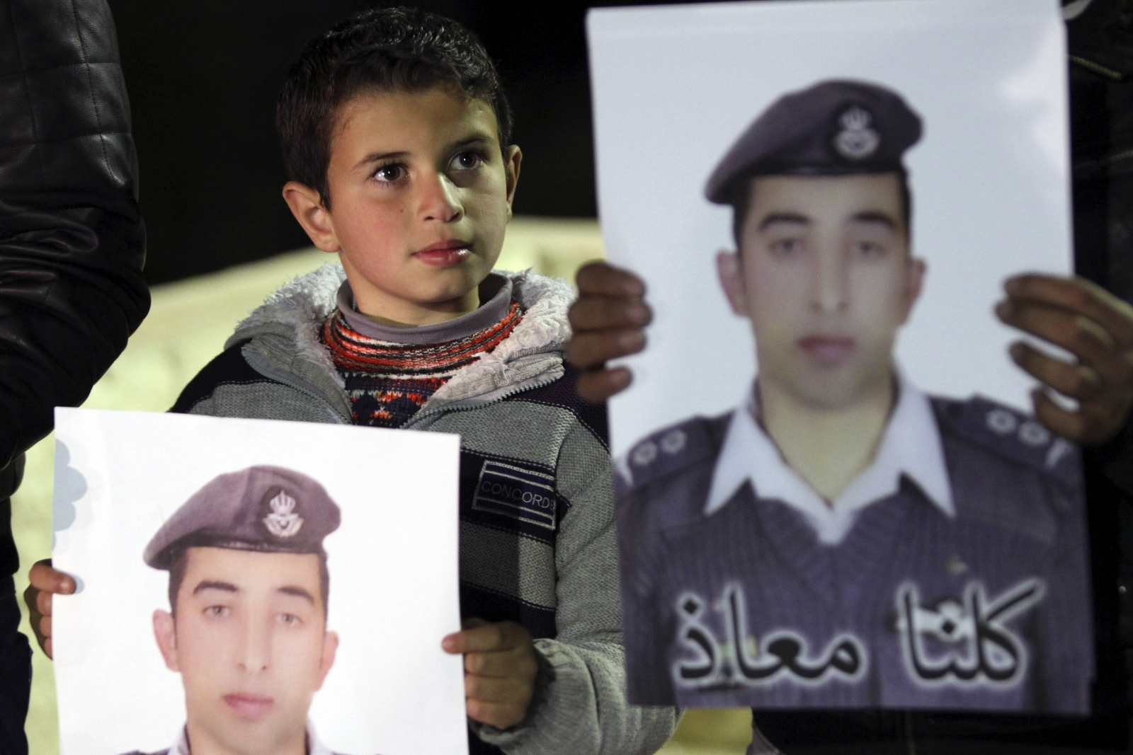 A relative holds a picture of Jordanian pilot Muath al-Kasaesbeh, who was captured by Islamic State after his plane crashed in Syria