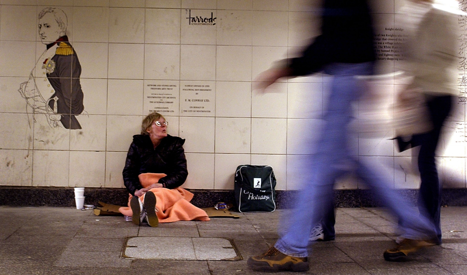 A homeless woman begs for change in a subway station