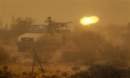 Libyan rebels fire an anti-aircraft gun at government forces during a heavy sandstorm near the village of Tiji in western Libya