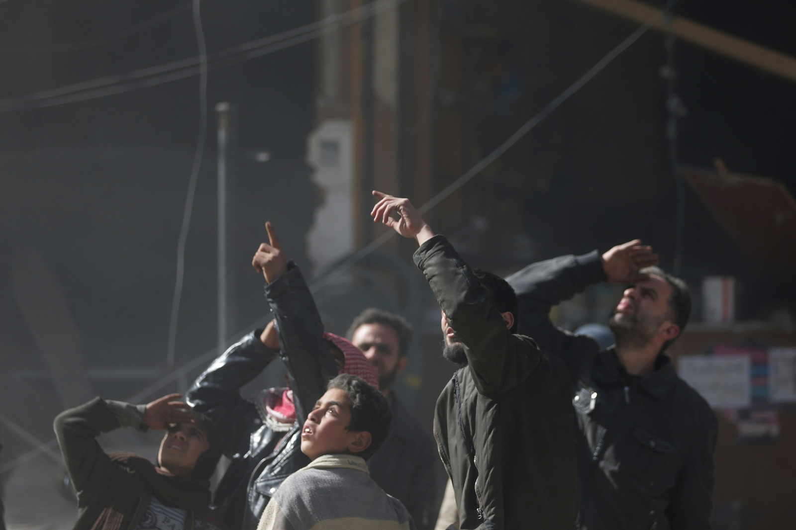 Residents react and gesture to the sky, during what activists said were seven air-strikes by forces loyal to Syria's President Bashar al-Assad, in Duma in Eastern Al-Ghouta