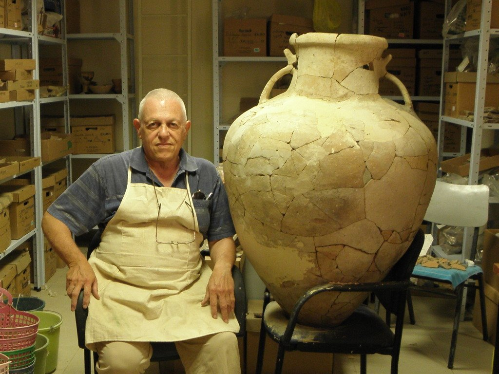 An archaeologist sits next to the large earthenware Cypriot pithoi from 17th century BC that he restored