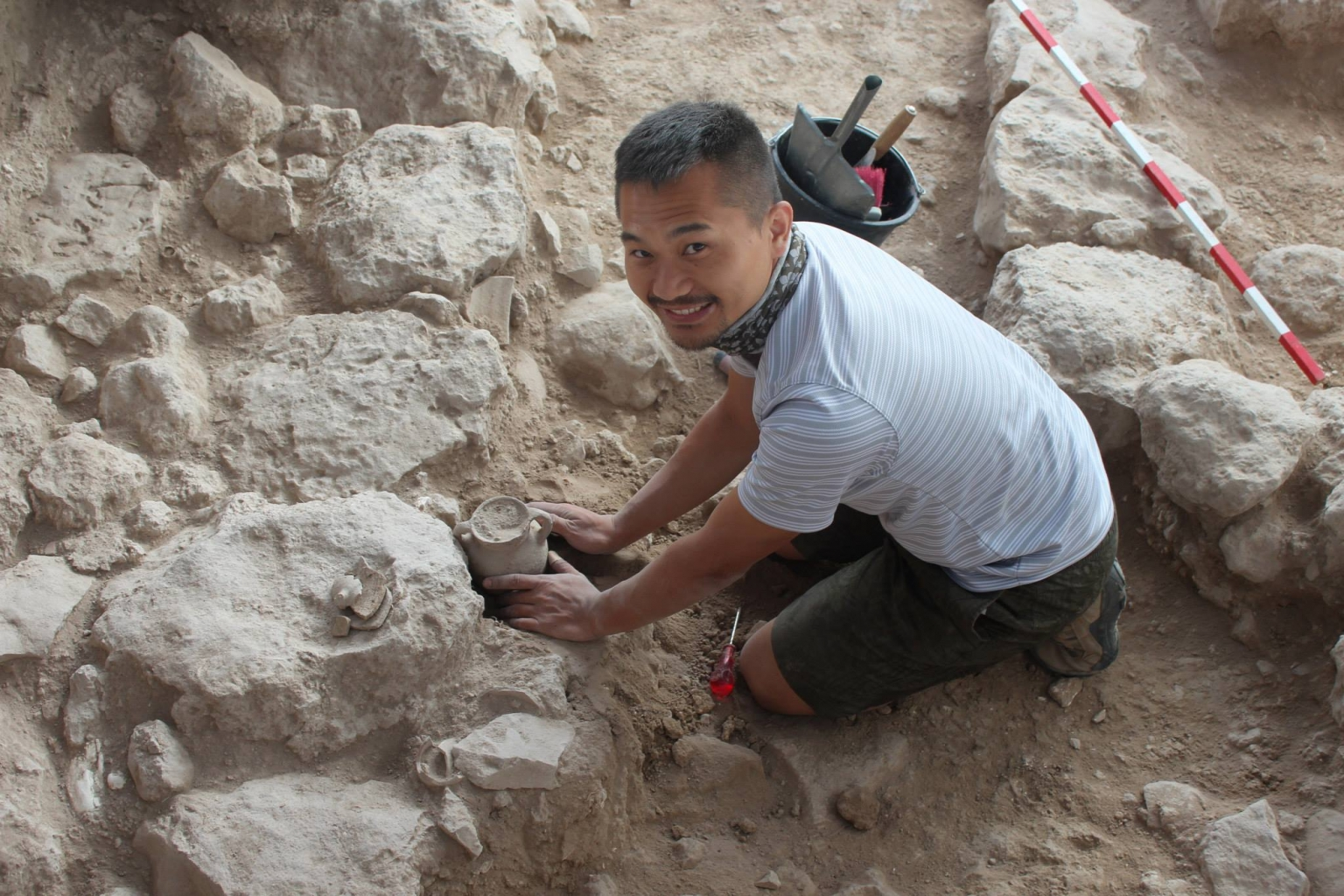 Archaeologist Benjamin removing a complete cooking jug from the fortifications in section Iron IIB