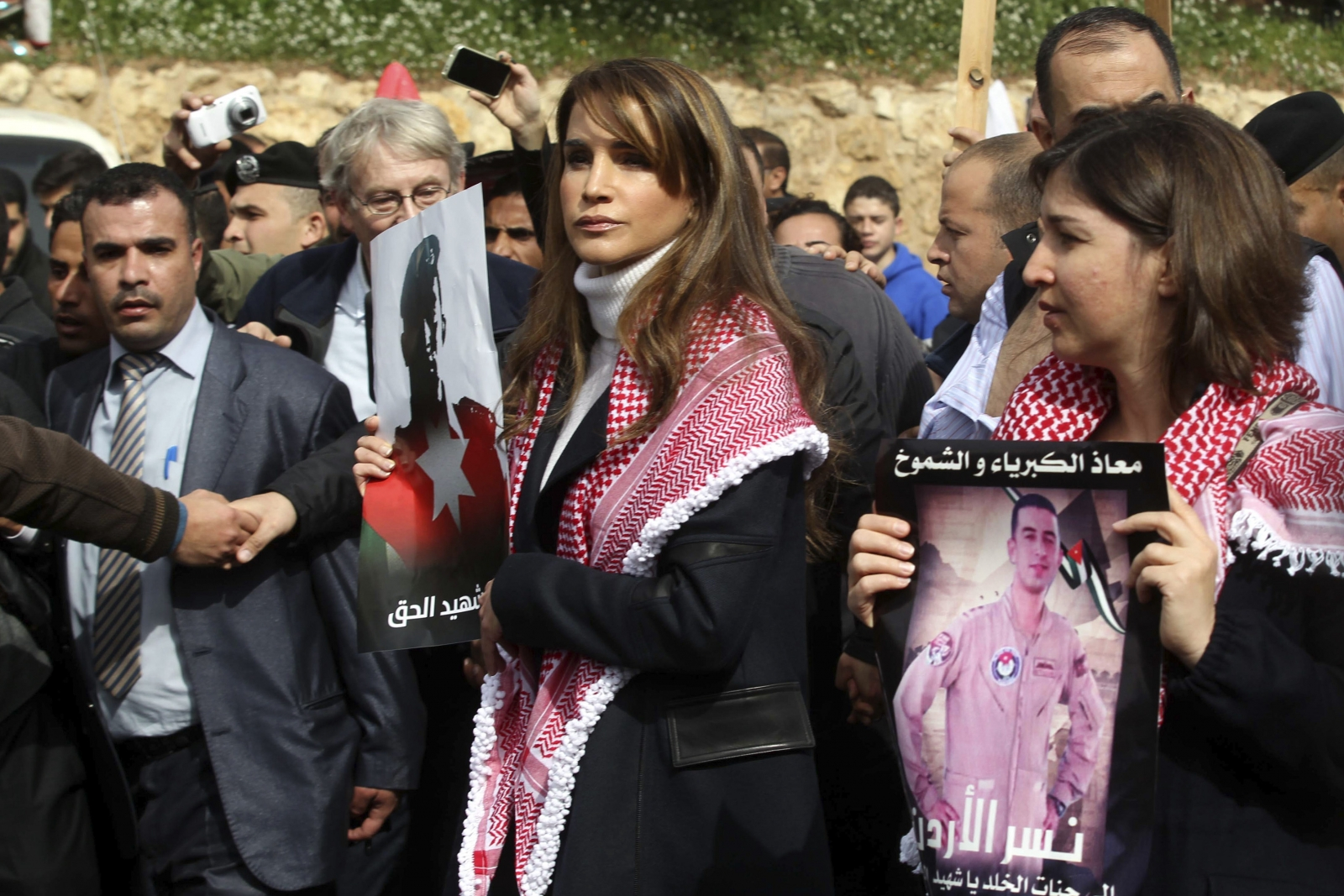 Jordan's Queen Rania (C) holds a picture of recently executed Jordanian pilot Muath al-Kasasbeh, with the words in Arabic reading