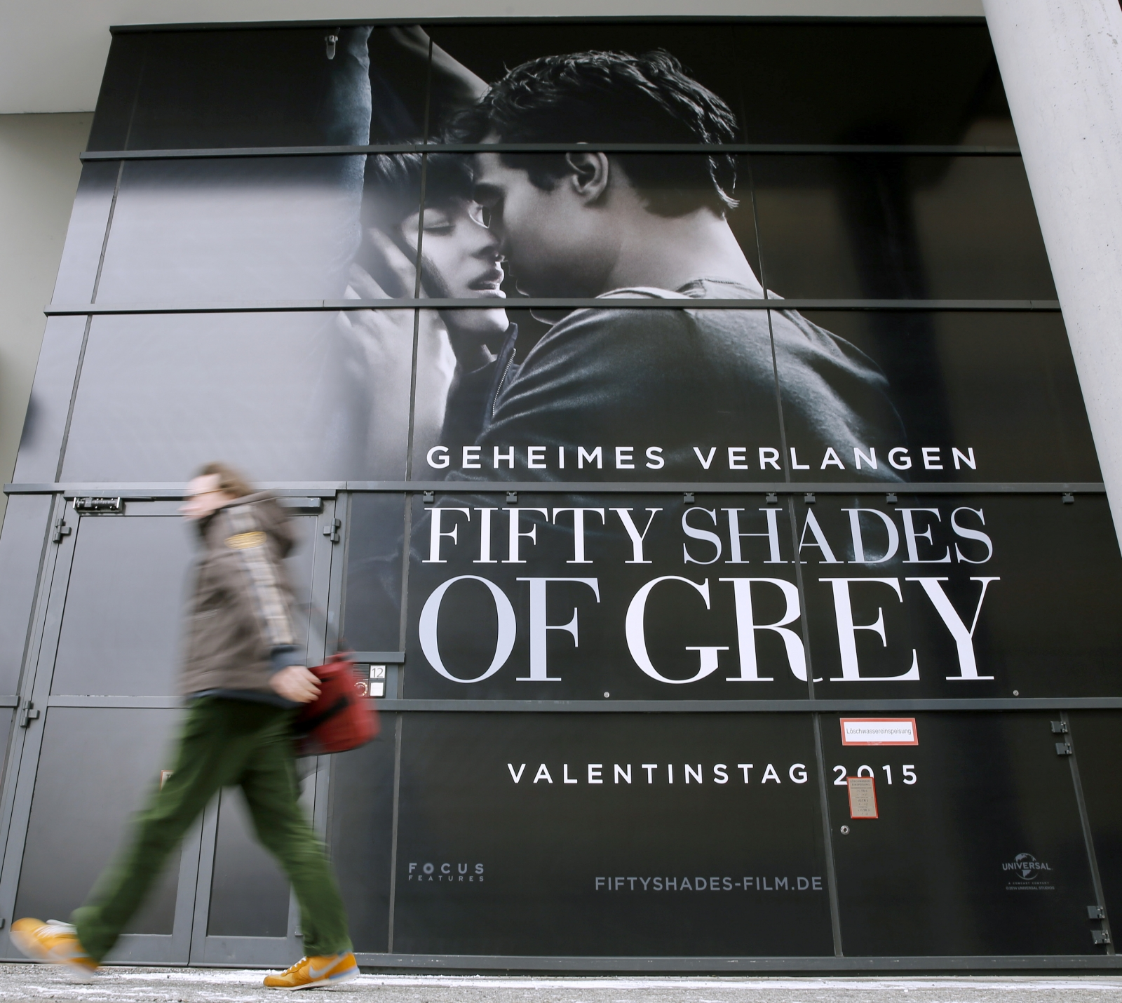 A pedestrian walks past an advertising placard for the movie 'Fifty Shades of Grey'