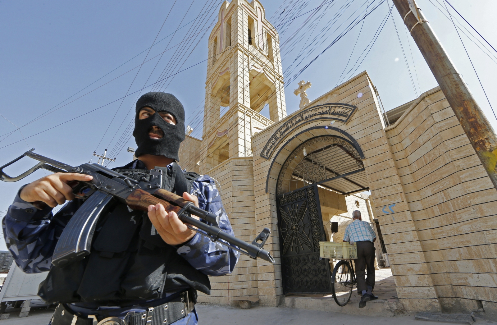 An Iraqi security officer, stands guard outside the Church of the Virgin Mary in the northern town of Bartala east of the northern city of Mosul (Getty)