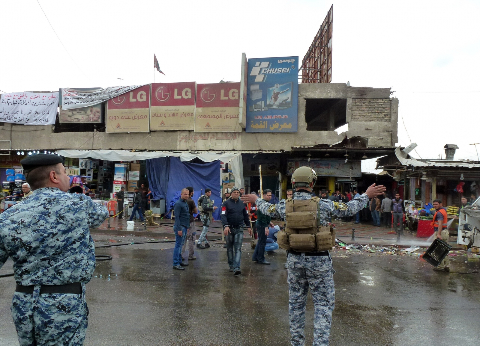 Iraqi police clear pedestrians of a street after a suicide bomber detonated explosives inside a restaurant in Baghdad al-Jadida, east of the capital,