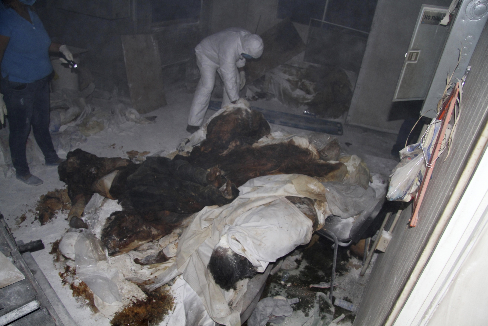 Forensic technicians stand near dead bodies at a crematorium