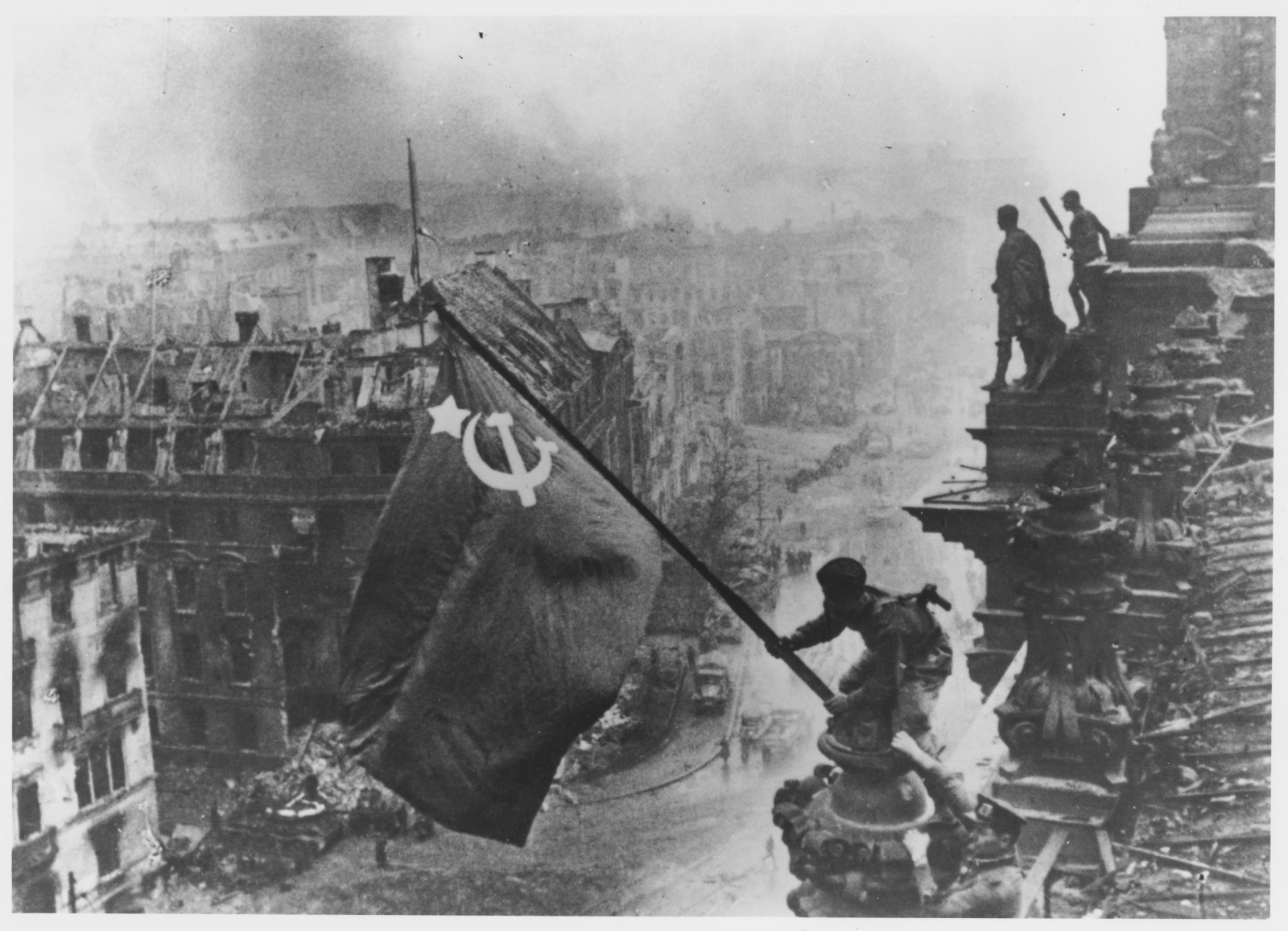 Russian soldiers flying the Red Flag, made from table cloths, over the ruins of the Reichstag in Berlin