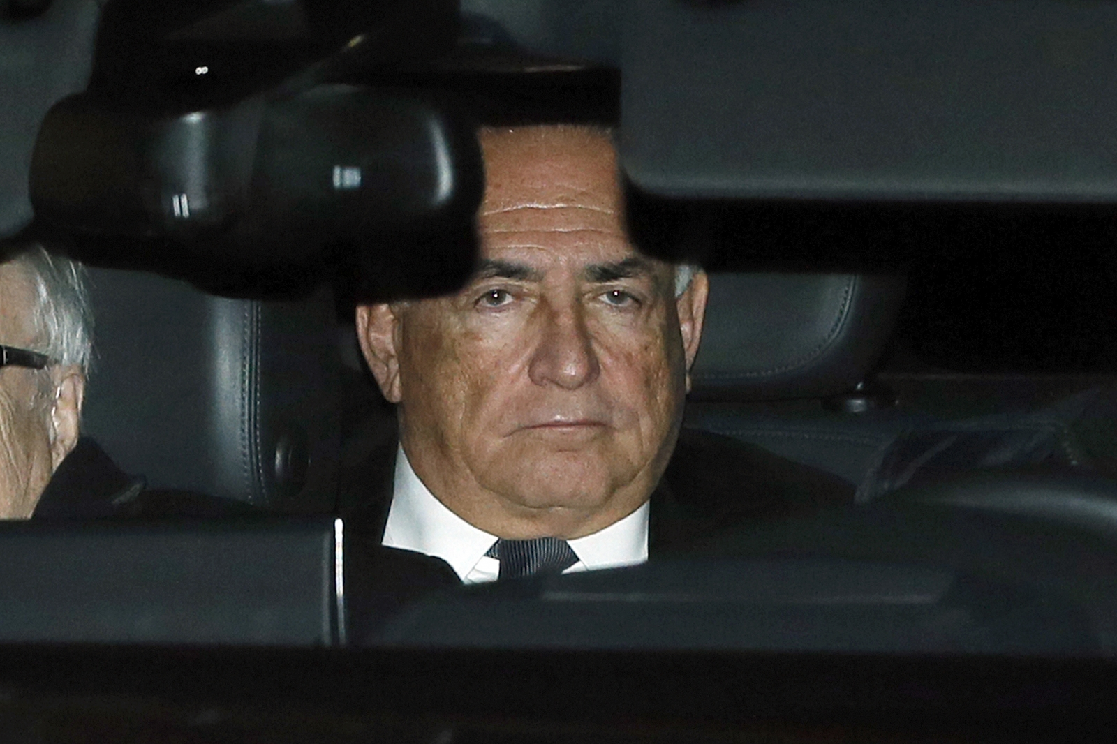Former IMF head Dominique Strauss-Kahn rides in the backseat of a car as he leaves after the first day of trial in the so-called Carlton Affair, in Lille